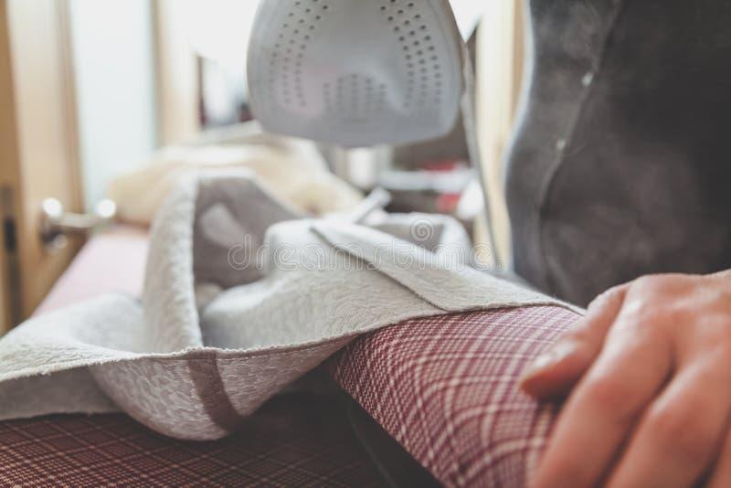 Het gladmaken van naad van kledingstuk met modern ijzer stock afbeeldingen