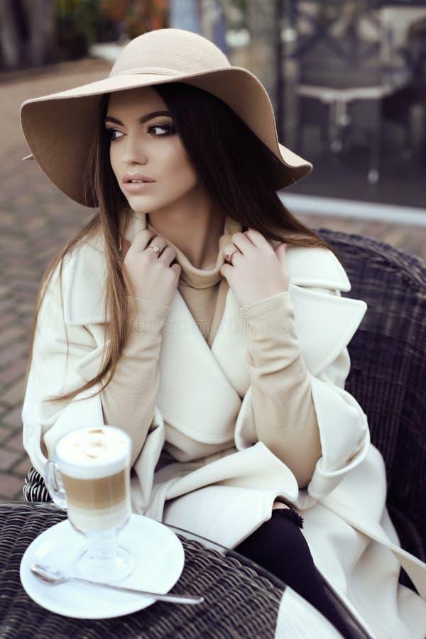 Het glamourmeisje met donker recht haar draagt luxueuze beige laag met elegante hoed royalty-vrije stock afbeeldingen