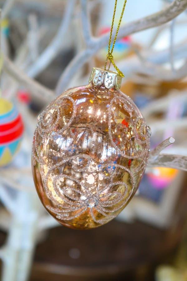 Het glanzende glittery gouden Oostelijke ornament hangt door een gouden koord van witte takken met andere kleurrijke erachter vag stock foto's