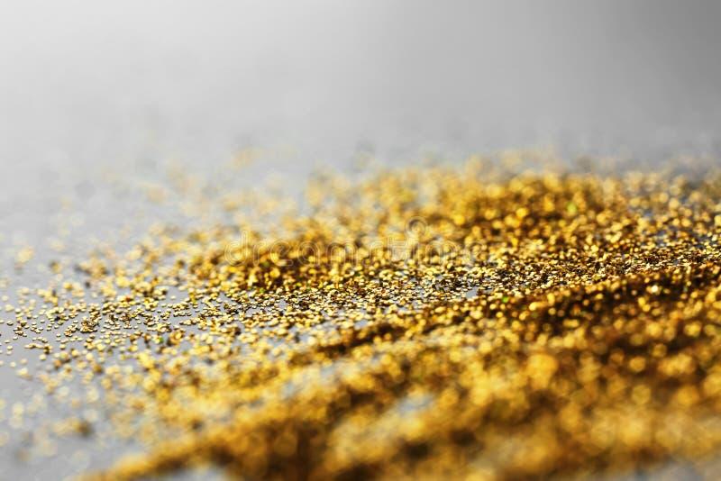Het glanzende goud schittert op grijze achtergrond stock fotografie