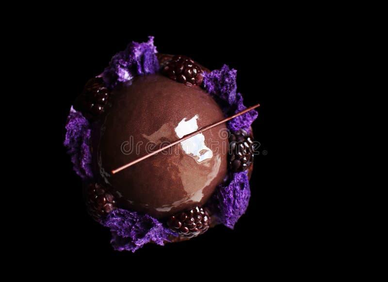 Het glanzende verglaasde chocolade en braambessendessert met purpere microgolf sponst en verse bessen op zwarte achtergrond af stock foto