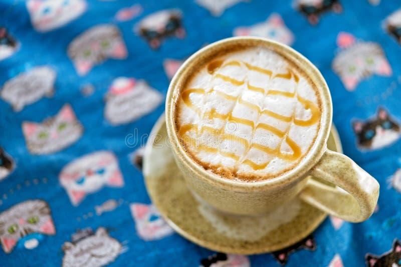 het glas de hete koffie van karamelmacchiato wordt bedekt door een dichte romige schuim en karamelsaus op lijst Hoogste mening en royalty-vrije stock foto's