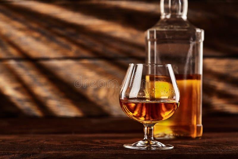 Het glas en de fles Cognac wodden lijst Houten achtergrond stock afbeelding