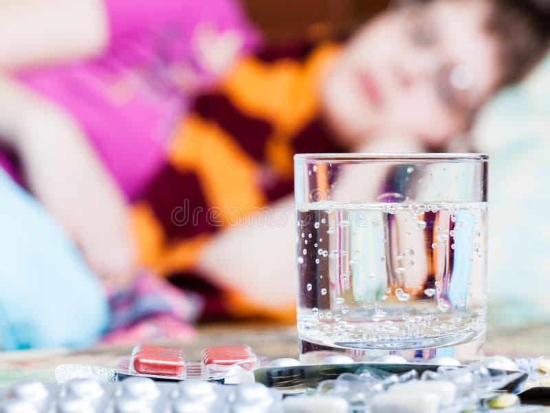 Het glas en de pillen op lijst sluiten omhoog en zieke vrouw royalty-vrije stock afbeeldingen