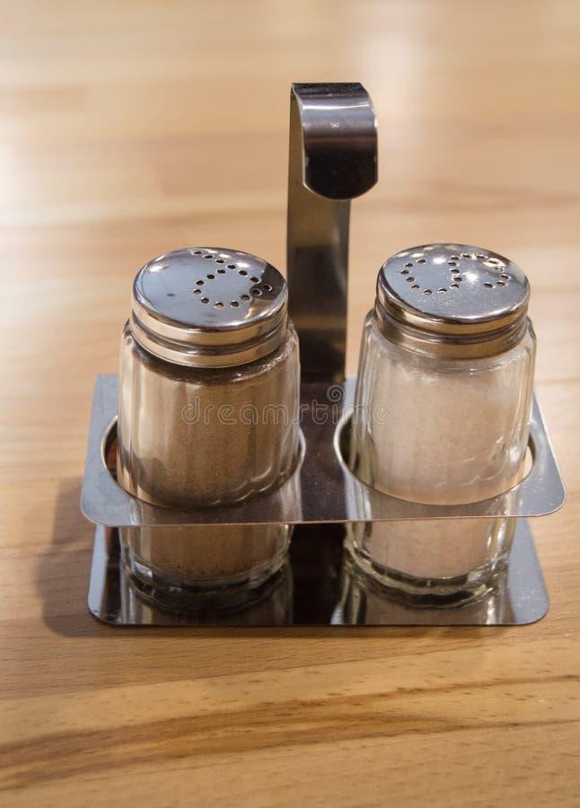 Het glas en de schudbeker van de van het metaalzout en peper die op houten lijst in koffie wordt geplaatst, sluiten omhoog, verti stock fotografie