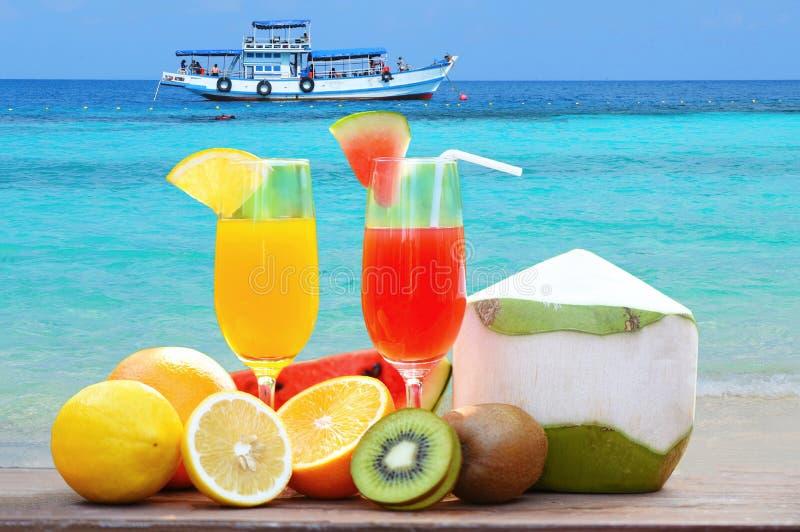 Het glas gezond voedsel van het de zomersap/velen rijp die fruit op het strand blauwe overzees wordt gemengd royalty-vrije stock foto's