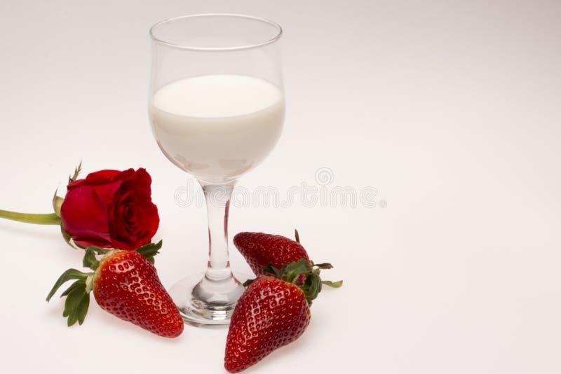 Het glas melk met aardbeien en nam toe stock fotografie