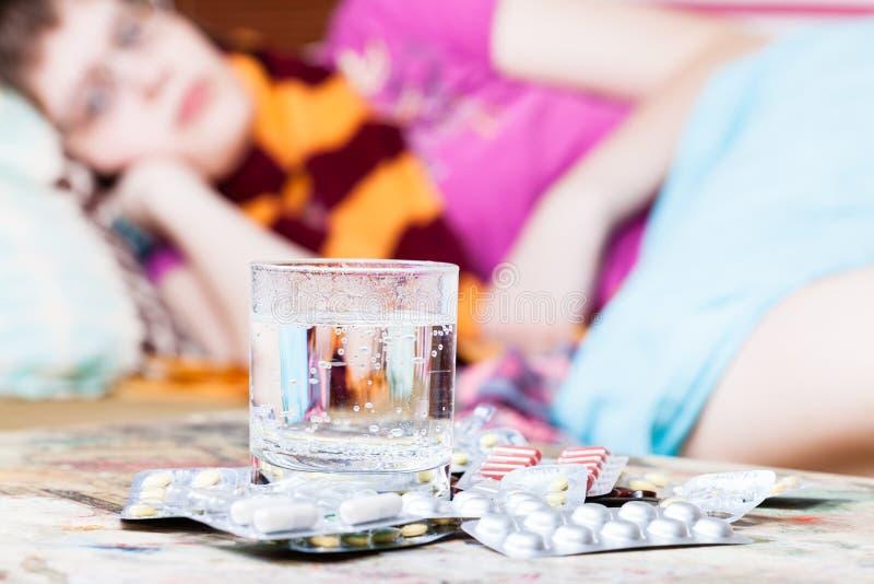 Het glas met water en de pillen sluiten omhoog en ziek meisje royalty-vrije stock fotografie