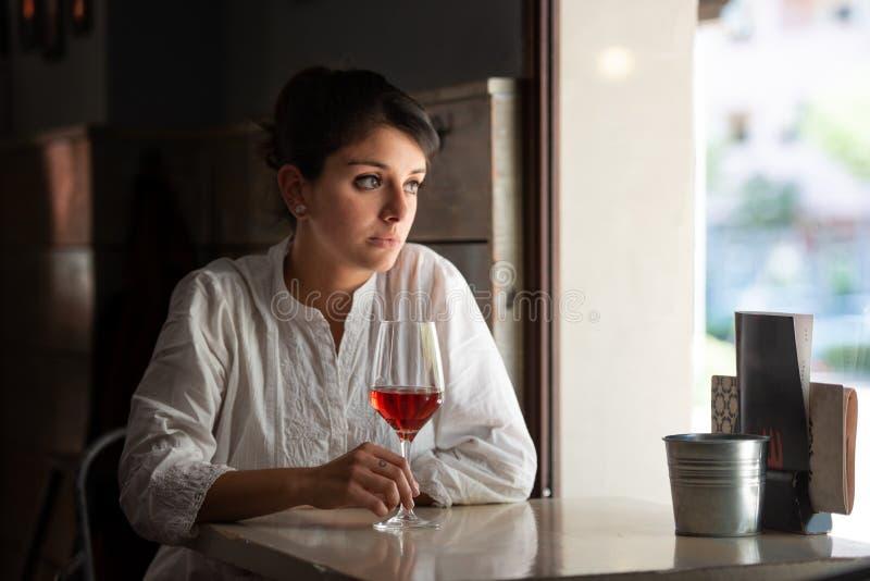 Het glas roze wijn wordt gehouden door een donker-haired meisje door een barvenster royalty-vrije stock afbeeldingen