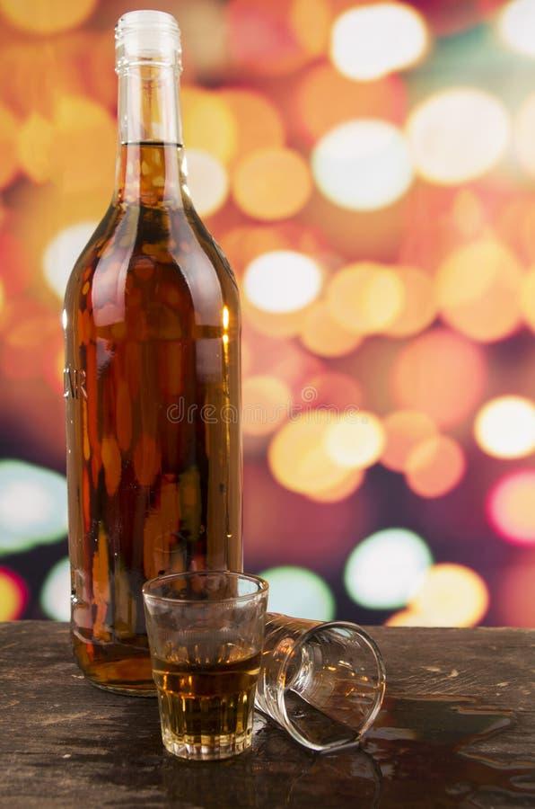 Het glas rumwhisky defocused over lichten stock afbeelding