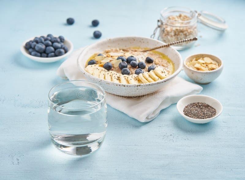 Het glas schoon water en de gezonde voeding ontbijten met havermeel, bosbessen, banaan op blauwe lichte achtergrond Zachte nadruk stock foto