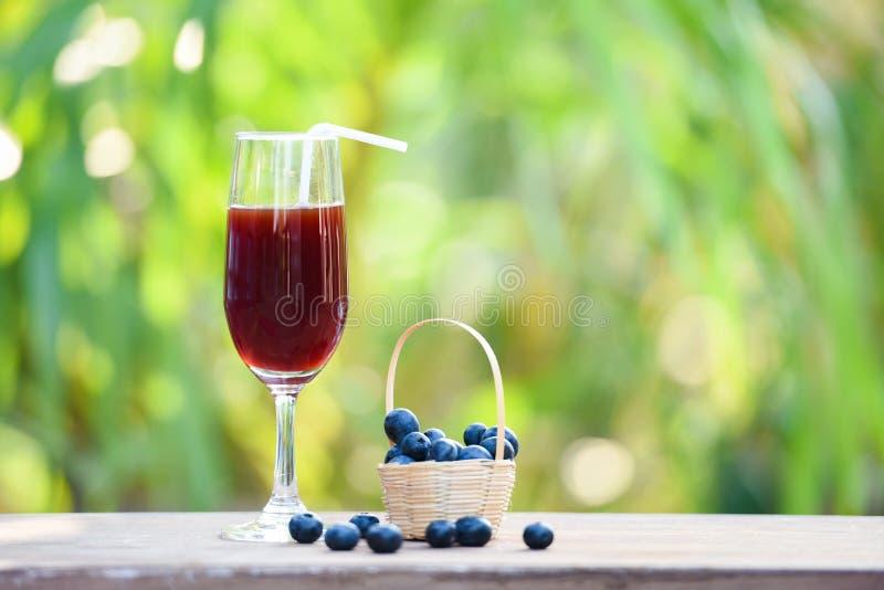 Het glas van het bosbessen smoothie sap en vers bosbessenfruit in mand met de aard groene zomer stock afbeelding