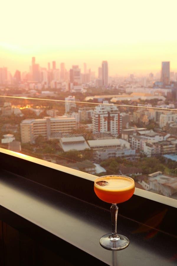 Het glas van cocktail op het dak versperde lijst met lucht stedelijke mening op achtergrond royalty-vrije stock foto