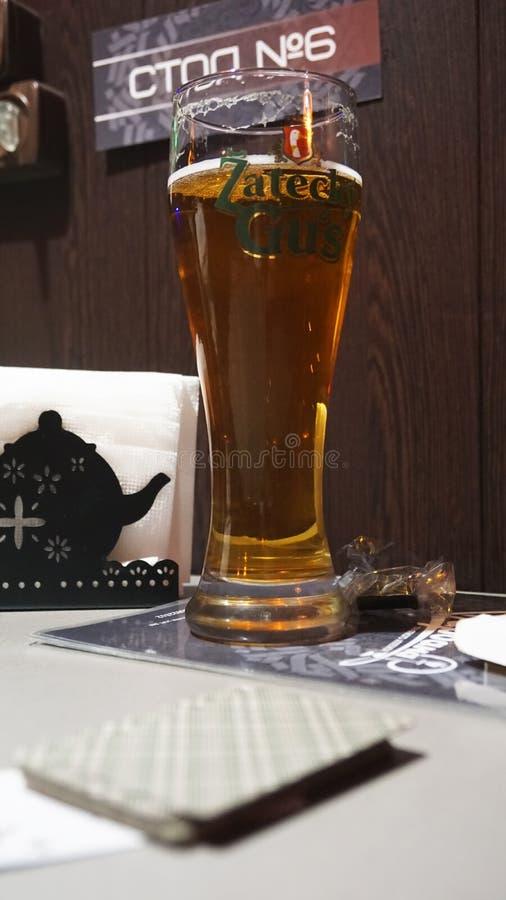 Het glas van de alcohol van de bierdrank is op de lijstspeelkaart stock foto