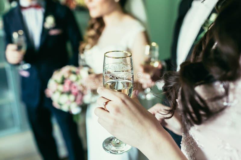 Het glas van de bruidsmeisjeholding met champagne op huwelijk stock foto