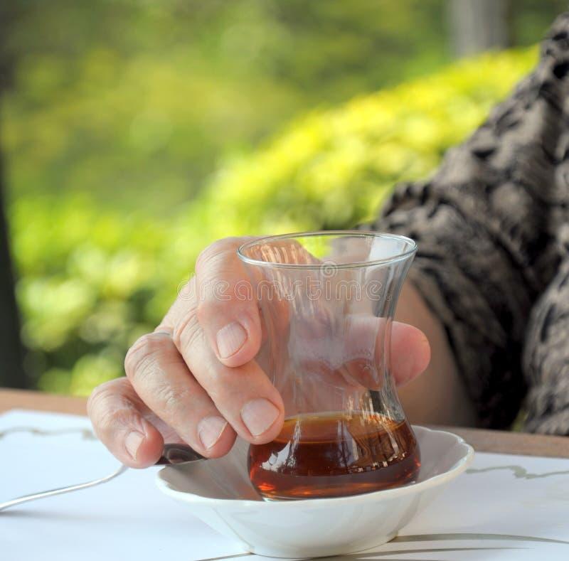 Het glas van de de holdingsthee van de hand royalty-vrije stock afbeelding
