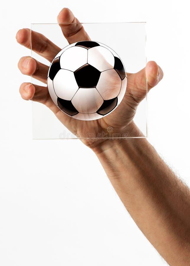 Het glas van de handholding met het beeldverhaal van de voetbalbal stock foto's