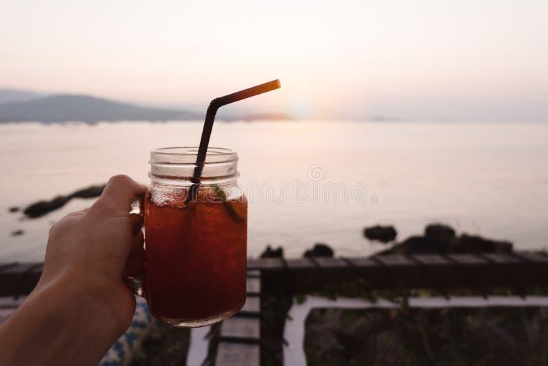 Het glas van de handholding de thee van het citroenijs op tropisch overzees strand in zon stock afbeeldingen