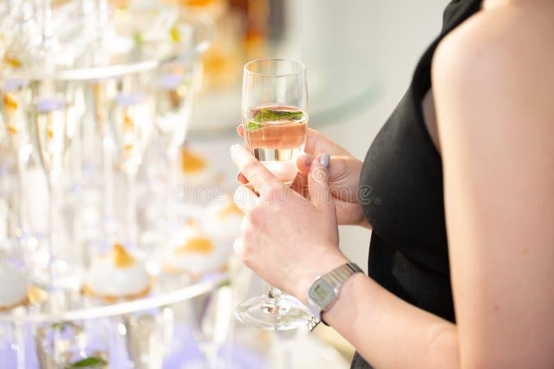 Het glas van de vrouwenholding van champagne en het roosteren, gelukkig feestelijk ogenblik stock foto's
