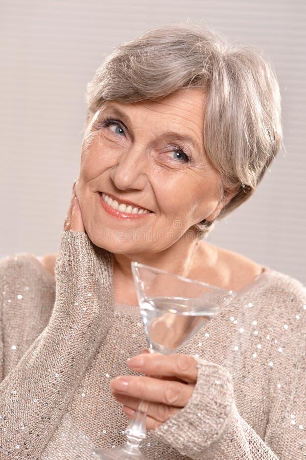 Het glas van de vrouwenholding van martini stock afbeelding