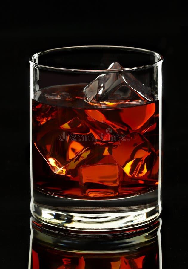 Het glas van de whisky op zwarte achtergrond stock foto