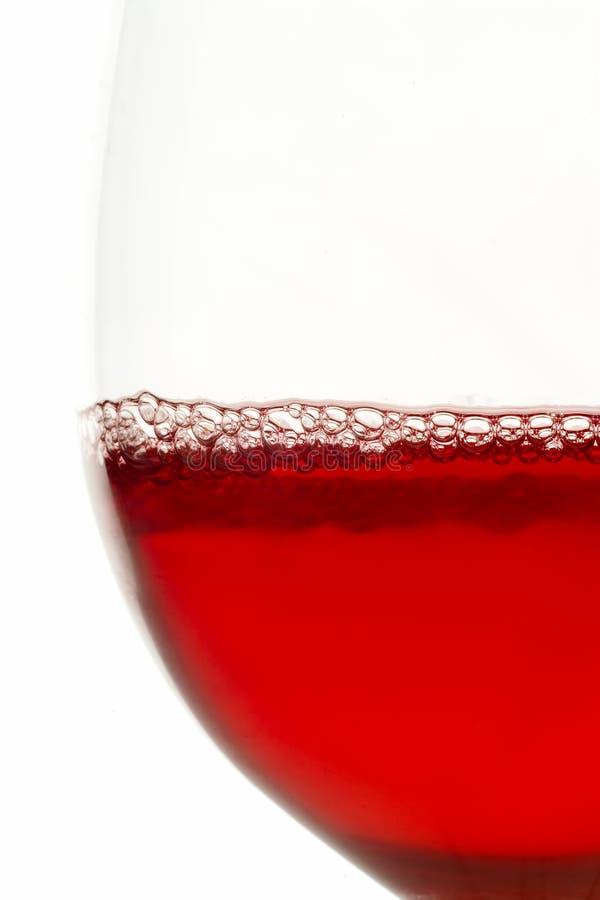 Het glas van de wijn dat met rode wijn wordt gevuld stock foto