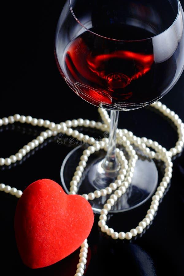 Het glas van de wijn en een rood hart stock foto's