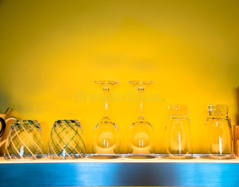 Het glas van de wijn op plank met gele achtergrond royalty-vrije stock afbeeldingen