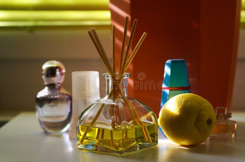 Het glas van geurdiffusor met rietstokken tussen parfum die flacons natuurlijke geur van citroen geven royalty-vrije stock foto
