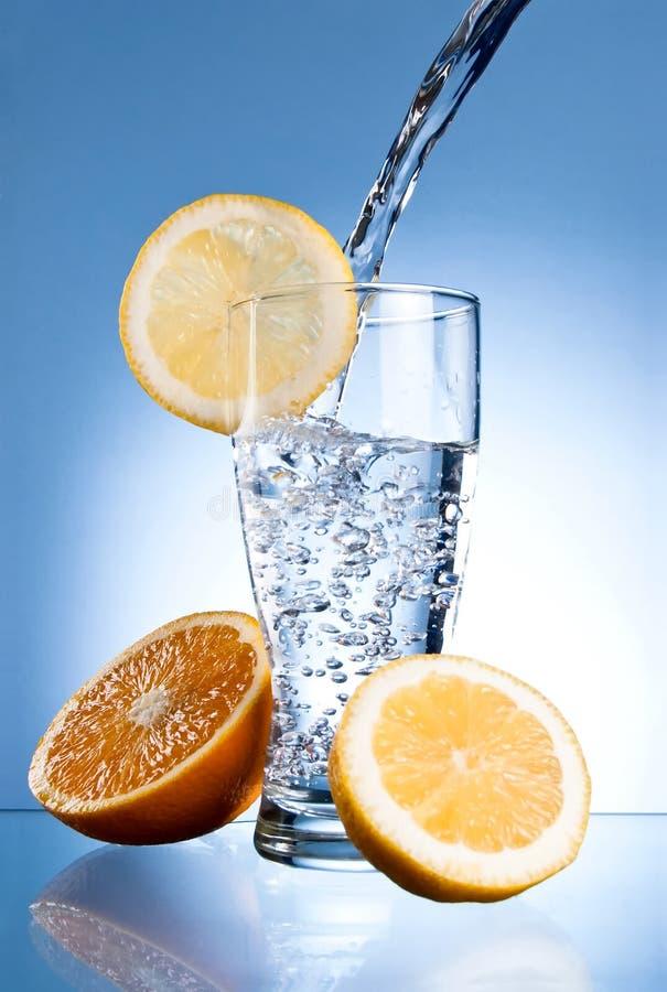 Het glas van het mineraalwater met citroen en sinaasappel royalty-vrije stock afbeelding