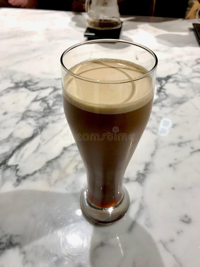 Het glas van Nitrokoude brouwt Koffie op Marmeren Oppervlakte Klaar te dienen royalty-vrije stock afbeeldingen