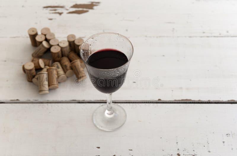Het glas van rode wijn en stapel van kurkt stock foto's