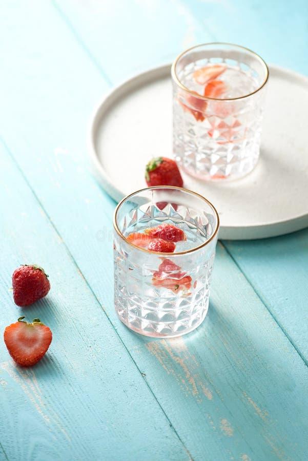 Het glas van vers, koude goot water met verse aardbeien en verse aardbeien naast het stock fotografie