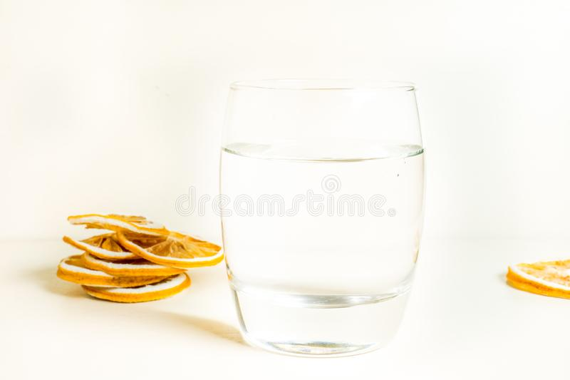 Het glas water isoleerde witte achtergrond met droge citroenplak in de achtergrond Sluit omhoog geschoten stock afbeeldingen