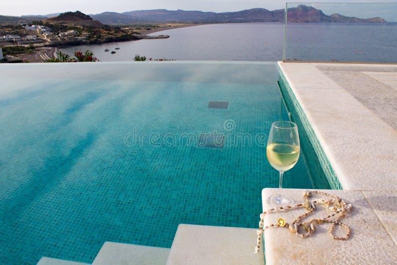 Het glas witte wijn met shell parels wordt gevestigd op de rand van de pooltreden royalty-vrije stock foto