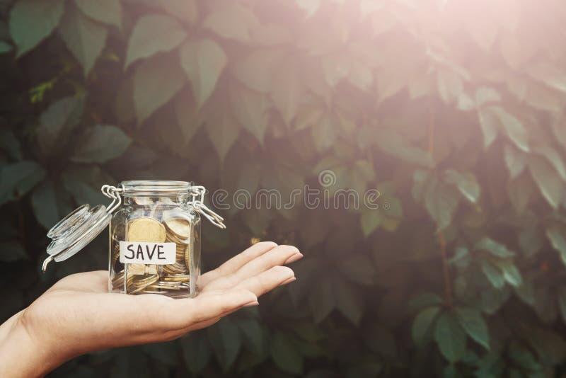 Het glaskruik van de handholding met muntstukken met SAVE etiket royalty-vrije stock afbeeldingen