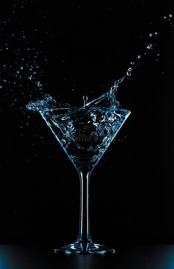Het glasplons van cocktailmartini op zwarte achtergrond royalty-vrije stock foto