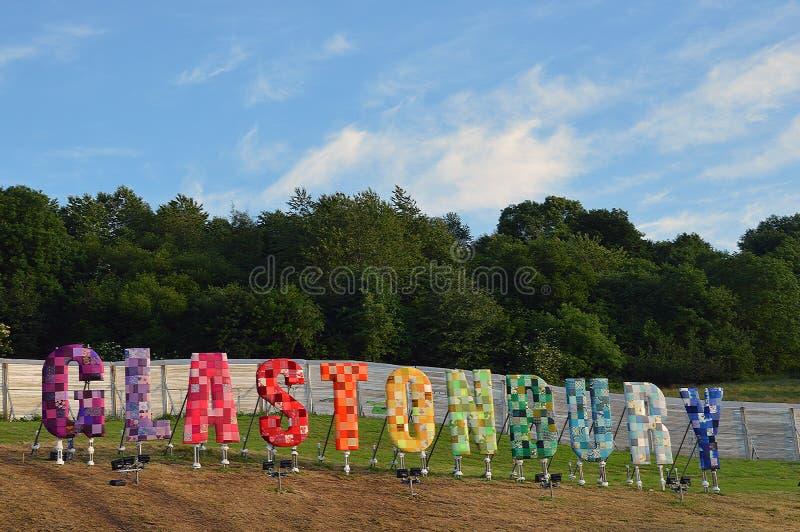 Het Glastonbury-Festivalteken met een blauwe erachter hemel en witte wolken stock fotografie