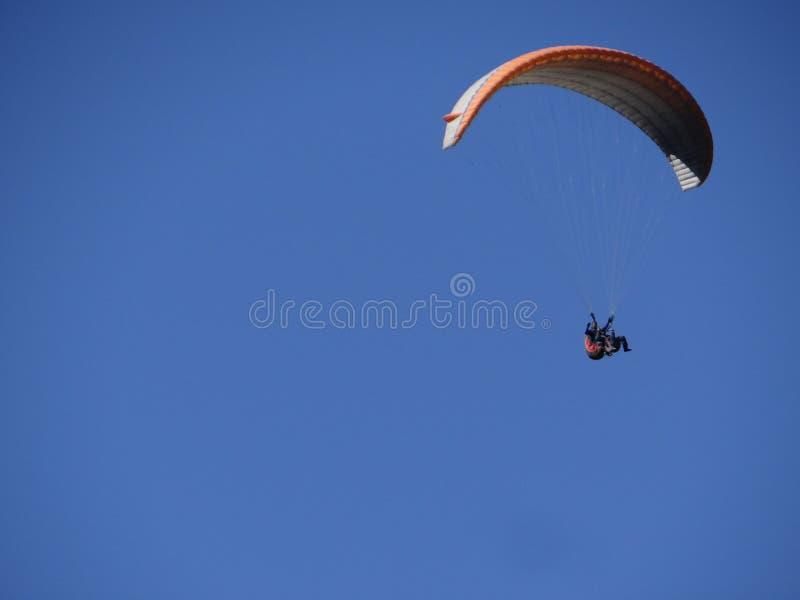 Het glijscherm vliegt hoog omhoog in de blauwe hemel in middag en geniet van aard in zijn ware zelf stock foto