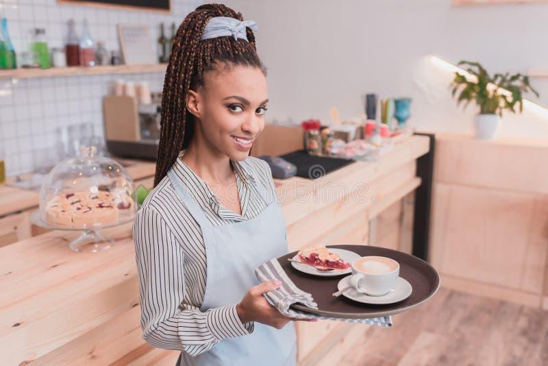 Het glimlachen Afrikaanse Amerikaanse barista die een dienblad met kop van koffie en pastei houden royalty-vrije stock fotografie