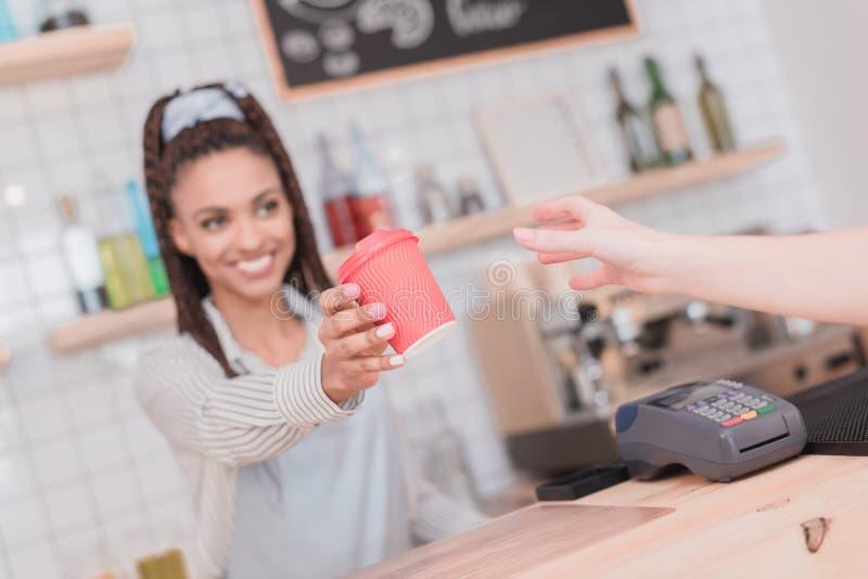 Het glimlachen Afrikaanse Amerikaanse barista die klant een beschikbare kop geven royalty-vrije stock afbeeldingen