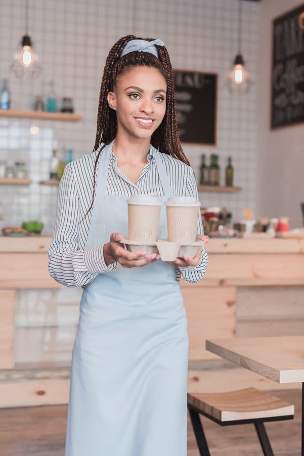 Het glimlachen Afrikaanse Amerikaanse barista die twee document koppen van koffie in een houder houden royalty-vrije stock afbeeldingen
