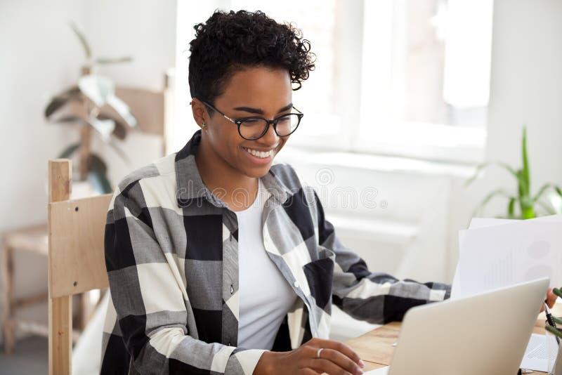 Het glimlachen het Afrikaanse Amerikaanse vrouwelijke werk met laptop en documenten stock foto