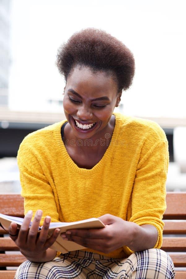 Het glimlachen Afrikaanse Amerikaanse vrouwenzitting buiten en lezing een boek royalty-vrije stock afbeelding