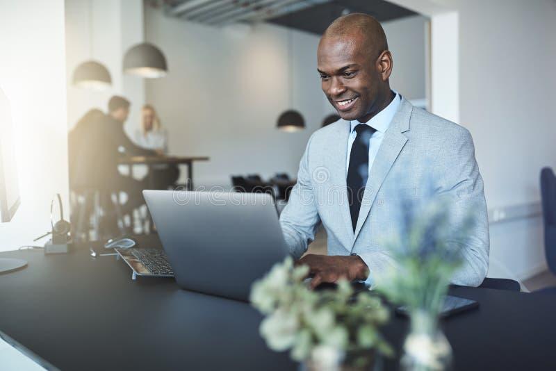 Het glimlachen Afrikaanse Amerikaanse zakenmanzitting op het werk die een overlapping gebruiken royalty-vrije stock foto's