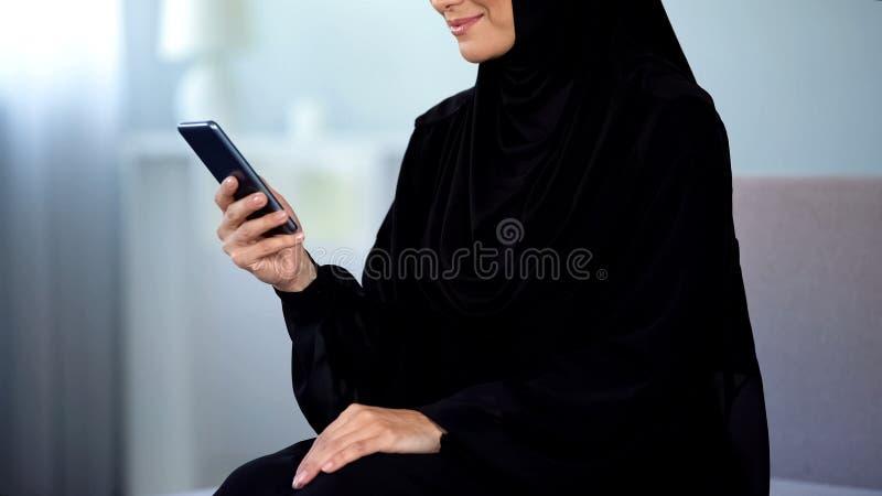 Het glimlachen Arabisch smartphonebericht van de vrouwenlezing, online mededeling, het babbelen stock afbeelding