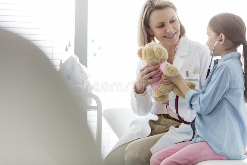 Het glimlachen arts geven teddybear aan meisje bij het ziekenhuis stock fotografie
