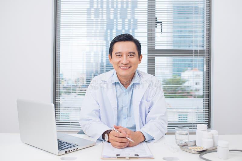 Het glimlachen Aziatische artsenzitting bij zijn bureau in medisch bureau royalty-vrije stock afbeelding
