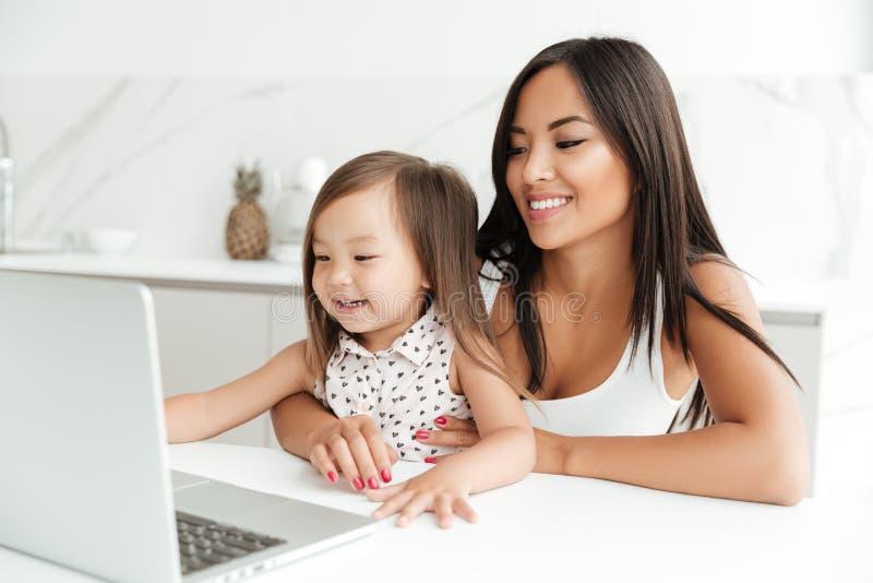 Het glimlachen Aziatische moederzitting met haar weinig dochter en samen het gebruiken van laptop stock afbeeldingen