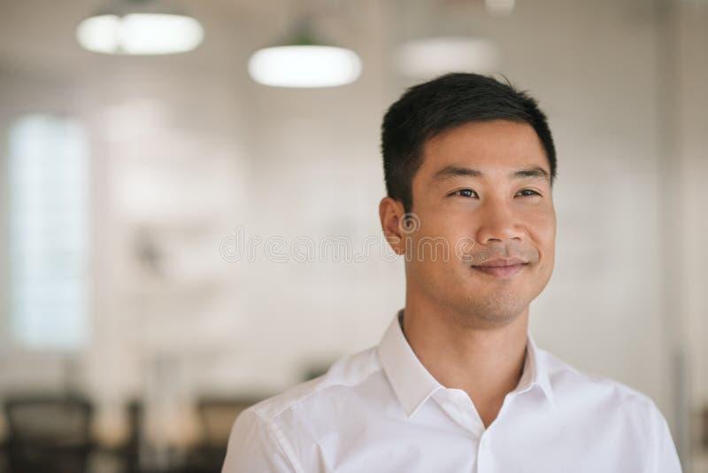Het glimlachen het Aziatische zakenman denken aan nieuwe ideeën in zijn bureau stock afbeeldingen
